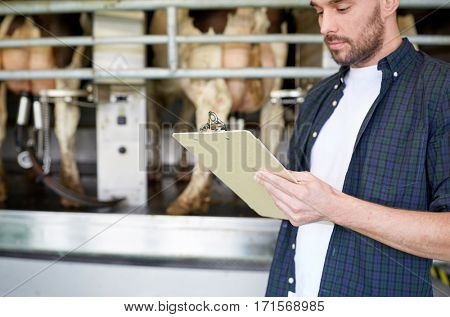 agriculture industry, farming, people, technology and animal husbandry concept - young man or farmer with clipboard and cows in cowshed on dairy farm