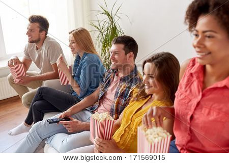 friendship, leisure, junk food, people and entertainment concept - happy friends eating popcorn and watching tv at home