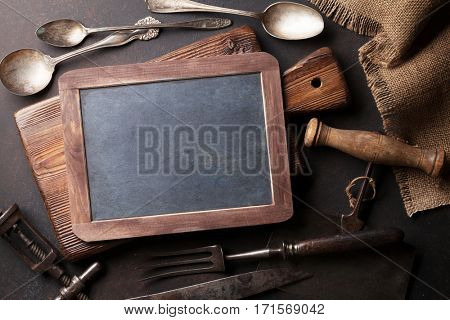 Old vintage kitchen utensils. Fork, knife, spoons, cutting board. Top view with chalk board for your text