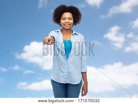 people, race, ethnicity, gesture and choice concept - happy african american young woman pointing finger to you over blue sky and clouds background