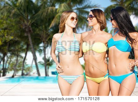 summer holidays, travel, people and vacation concept - happy young women in bikinis and shades over exotic tropical beach with palm trees and pool background