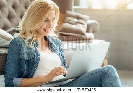 Do it. Young hardworking beautiful woman using her laptop while spending time at home and relaxing.