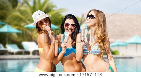 summer holidays, vacation, food, travel and people concept - group of smiling young women eating ice cream over exotic beach with palm trees and pool background