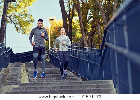 fitness, sport, people and lifestyle concept - couple running downstairs in city