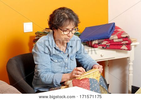 seamstress woman sewing for finish a quilt.