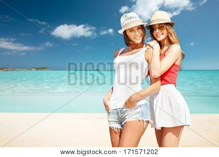 summer holidays, vacation, travel and people concept - smiling young women in hats and casual clothes over exotic tropical beach background