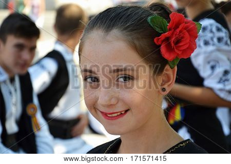 CLUJ-NAPOCA ROMANIA - AUGUST 04 2012: Young girl with red rose in her hair with a group of young people in the background dressed in Romanian traditional folk costumes rest in shadow on the street.