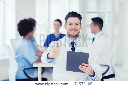 clinic, profession, people and medicine concept - happy male doctor with tablet pc computer over group of medics meeting at hospital showing thumbs up gesture