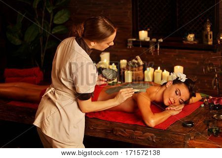Mud mask of woman in spa salon. Back massage with clay full body . Girl on interior with candles in oriental therapy room. Female with flower lying on wooden spa bed. Beautician used cosmetic brush.