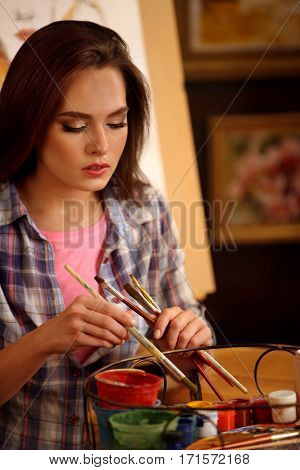 Artist painting on easel in studio. Girl paints portrait of woman with brush. Female painter seen from behind. Sad female thinks about choice of brushes. Indoor home interior for handmade crafts.