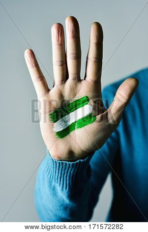 the flag of Andalusia, Spain, painted in the palm of a young caucasian man