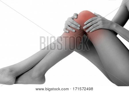 woman sitting and holding her beautiful healthy long leg with massaging knee and thigh in pain area black and white color with red highlighted Isolated on white background.