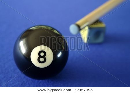 Pool ball, cue and chalk on blue table