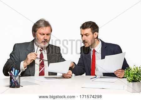 The two colleagues working together at office on white studio background. They actively and emotionally discussing current plans