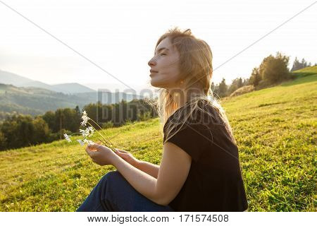 Young beautiful blonde girl enjoying mountains view, holding camomiles, sitting on grass. Copy space.