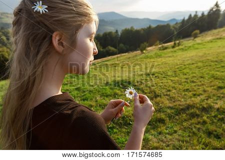 Young beautiful blonde girl holding camomiles, carpathian mountains background. Copy space.