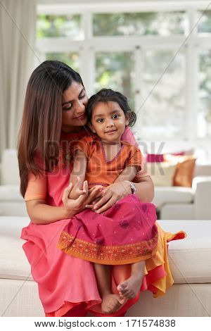 Little girl in traditional Indian clothing sitting on laps of her pretty mother while posing for photography against panoramic window of living room