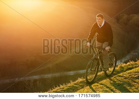 Mountain biker riding on bike in spring inspirational mountains landscape. Man cycling MTB on trail track. Sport fitness motivation and inspiration outdoors in sunset.
