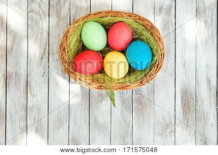 Easter eggs in basket on rustic wooden planks. Spase for text. Top view.