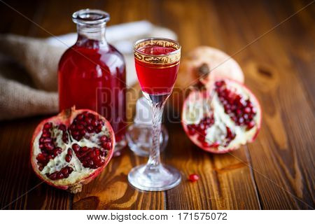 sweet pomegranate fruit alcoholic cordial in the decanter with a glass on a dark table