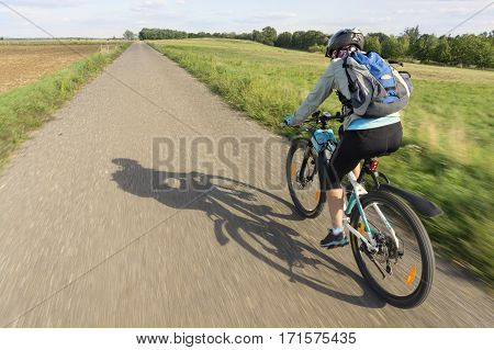 Woman bicyclists riding on country road. Natural motion blur.