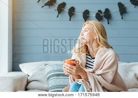 But coffee first. Overjoyed pretty young woman drinking coffee and posing while sitting in cozy bedroom.