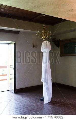 Beautiful white rustic wedding dress hanging on the chandelier in the room