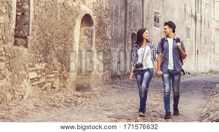 Traveling couple of hipsters: walking around old town. Vacation, summer, holiday, tourism: concept.