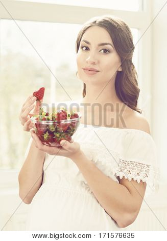Beautiful pregnant woman eating strawberries in kitchen. Motherhood, pregnancy, maternity concept.