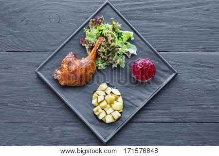 Roasted duck leg closeup served with apples and cherry sauce. Restaurant food on black square slate plate, top view on wood table background