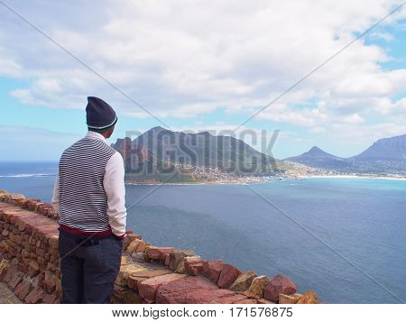 Contemplative African young man standing and looking at distance to the blue sea and thinking about something.