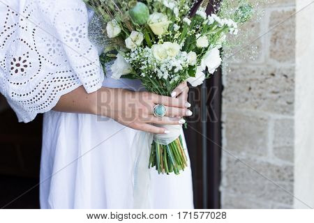 The ring with blue stone on the bride's finger. The bride in white wedding dress holds a wedding bouquet with white roses, poppies and greenery decorated with long silk ribbon