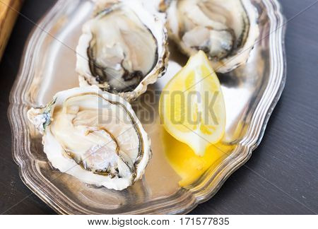 Raw fresh open oysters shells on silver plate close up