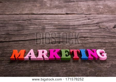 marketing word made from colored wooden letters on an old table. Concept