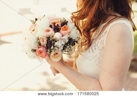 Tender Bride With Red Hair Holds A Pink Wedding Bouqet Of Ranunnculus