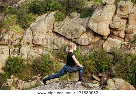 Beautiful sportive blonde girl training, stretching on rock in canyon. Copy space. poster