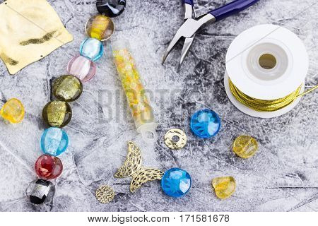 Jewelry making in process-glass beads metal components cord seedbeads pliers on the table. Hobby handmadefine arts. Selective focus.