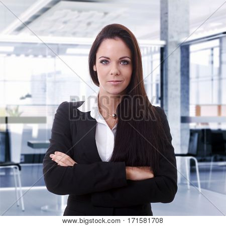 Portrait of confident young businesswoman, smiling, looking at camera.