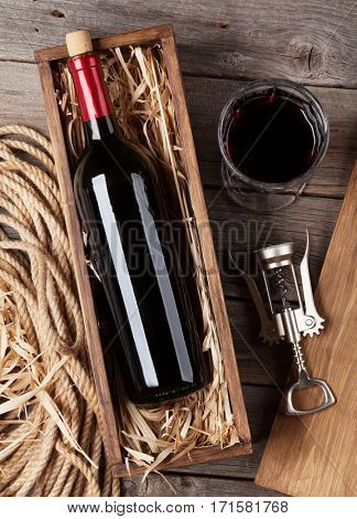 Red wine bottle and glass on wooden table. Top view
