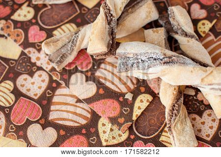 Cookies on dark napkin with image of hearts close up. Selective focus, top view.