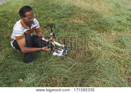 Portrait of middle-aged Indian man sitting on haunches and preparing quadcopter for the first fly on background of long grass