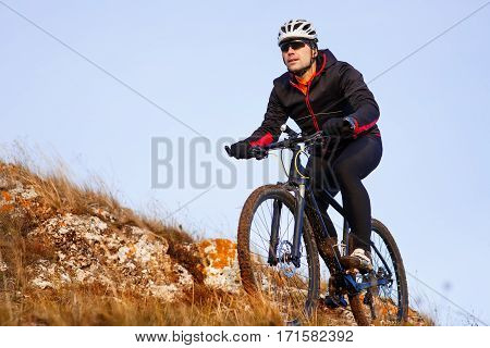 Cyclist in Black Jacket Riding the Bike on the Rocky Trail. Extreme Sport Concept. Space for Text. Cyclist in the helmet and black sunglasses. Hill and rocks. Background of blue sky. Travel in the countryside.