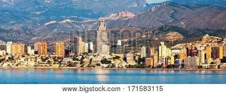 Benidorm Costa Blanca - a coastal town and popular touristic resort in province of Alicante Spain. Aerial view of city skyline formed by tall hotels and apartment buildings and mountains
