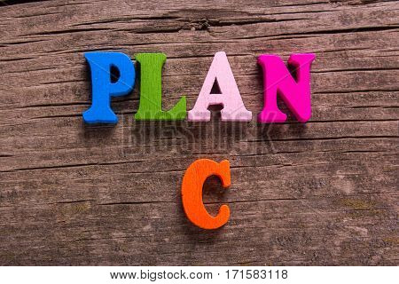 plan C word made from colored wooden letters on an old table. Concept