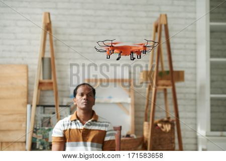Confident middle-aged Indian repairman looking at orange drone while testing it in workshop