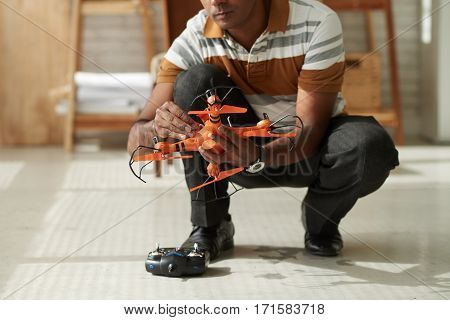 Middle-aged man sitting on haunches indoors while making adjustments in drone construction