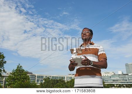 Cheerful Indian man in safety goggles standing in sunny park and holding drone remote controller in hands, blue sky observed on background