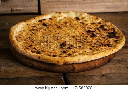 Garlic pizza bread on wood table with ingredients