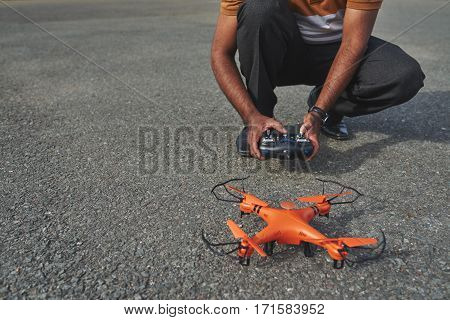 Man with remote controller in hands crouching next to small orange drone and preparing to launch it