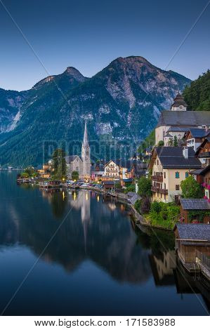 Scenic picture-postcard view of famous historic Hallstatt mountain village with Hallstattersee in the Austrian Alps in mystic twilight during blue hour at dawn in summer Salzkammergut region Austria